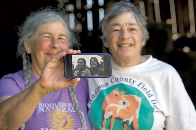 Cheesemakers Marjorie Susman (left) and Marian Pollack with a photo of themselves from the early days of Orb Weaver Farm - CALEB KENNA