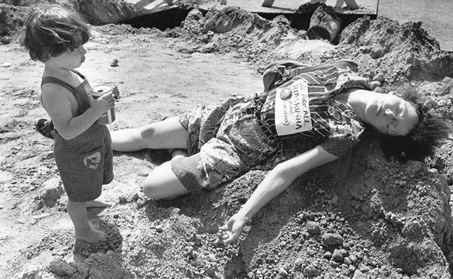 """Robin Lloyd with son Jesse at a """"die-in"""" during a renovation of Church Street. Her sign reads, """"We are all Hibakusha"""" (Hiroshima bomb survivors). - COURTESY OF JESSE LLOYD GUMA"""