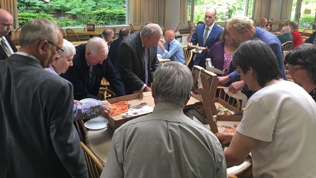 Legislators eating pizza during Friday's late night session. - JOHN WALTERS