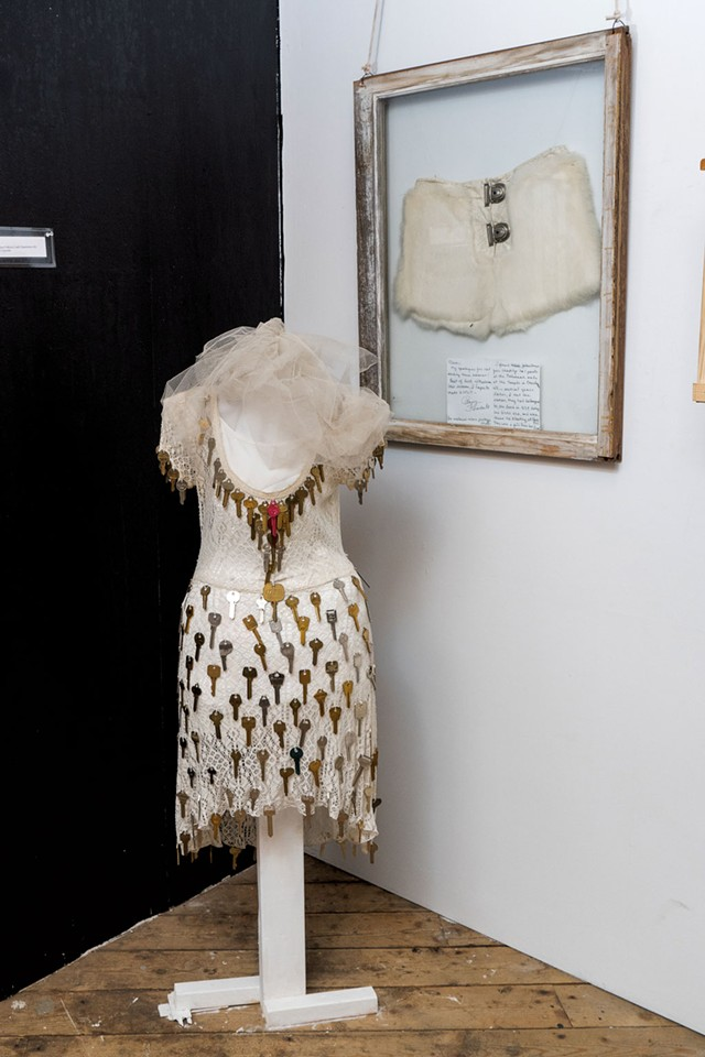 Installation with pair of white leather fetish pants, complete with a locking fly, on the wall - DON WHIPPLE