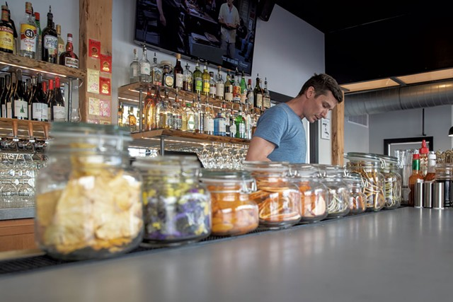 Bartender Woody Wright-Moore standing behind jars of housemade dried fruits used for custom cocktails - JAMES BUCK