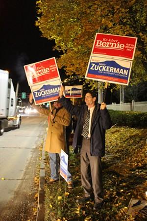 Lt. Gov. David Zuckerman, a Progressive/Democrat, and supporters wave to cars Monday night. - PAUL HEINTZ