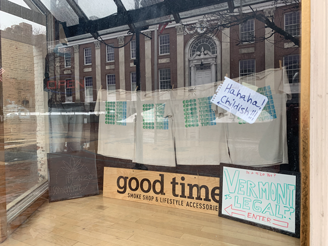 Burlington City Hall is reflected in Good Times Gallery's window. - JOHN JAMES