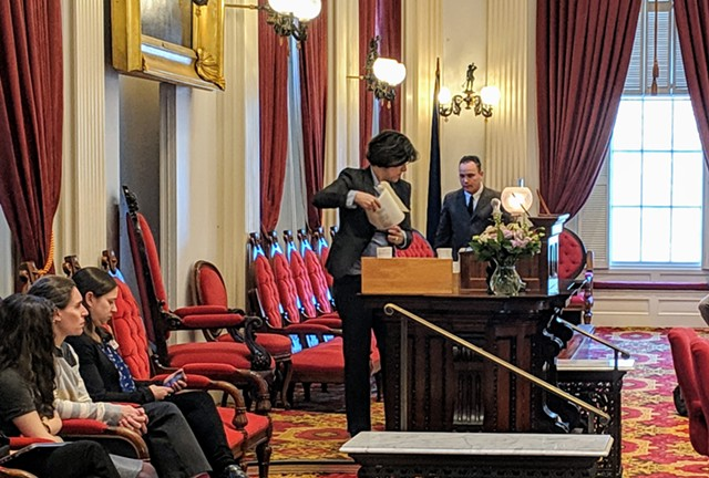 House Speaker Mitzi Johnson (D-South Hero) cleaned off her podium after accidentally smashing a glass lampshade with a gavel. - TAYLOR DOBBS