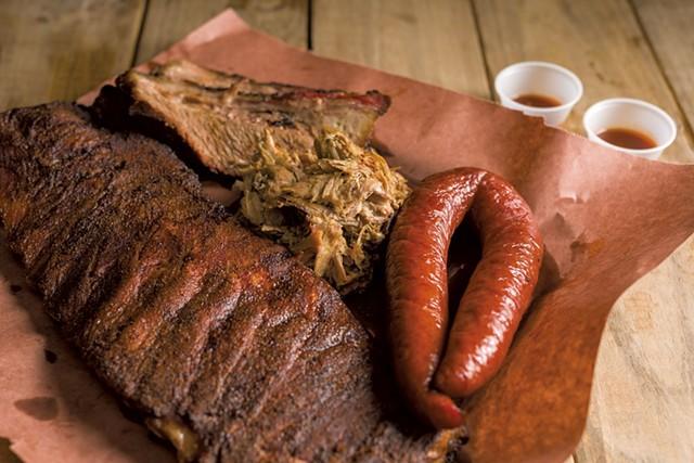 Smorgasbord of smoked meats: ribs, brisket, pulled pork and sausage - OLIVER PARINI