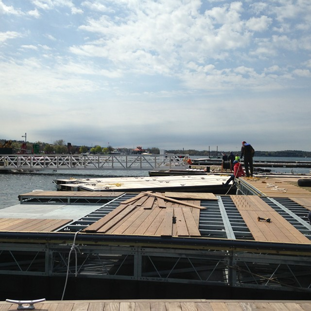Workers assemble docks and slips at the Burlington Harbor Marina. - MOLLY WALSH