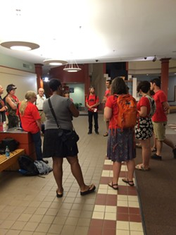 Critics of the rate increase Blue Cross Blue Shield requested gathered to debrief and sing. Many wore red shirts proclaiming that health care is a human right. - NANCY REMSEN