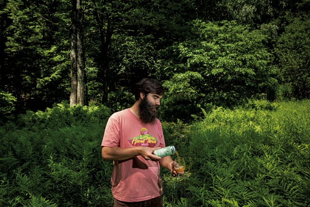 Christophe Gagné pouring a glass of Windham Flora while standing in the wilderness behind Hermit Thrush Cellars - ZACHARY P. STEPHENS