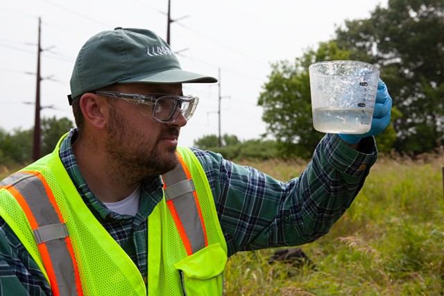 Aaron Sutton tests a well outside the Air National Guard base in Burlington last week. Sutton works for Parsons Corp., the environmental firm performing a range of tests to see if contamination on the base has migrated toward the Winooski River. - KEVIN MCCALLUM