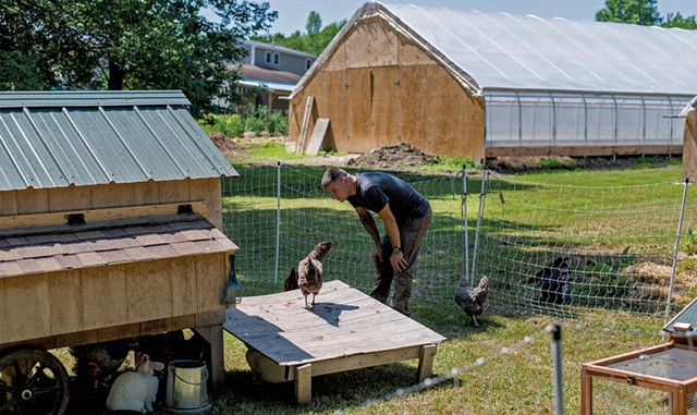 Kyle Bowley looking at chickens in a coop - GLENN RUSSELL