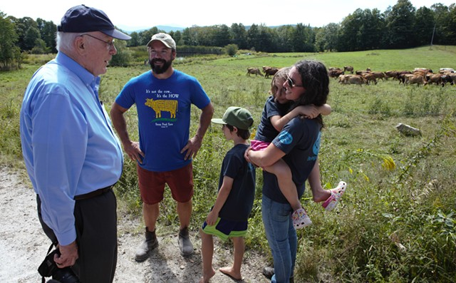 Leahy chats with the Webbs near their herd. - KEVIN MCCALLUM