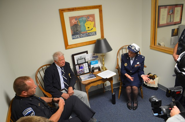 Roger Bourassa, center, and Rosanne Greco, right, debate the merits of their sit-in strategy with Burlington deputy police chief Jon Murad - DEREK BROUWER