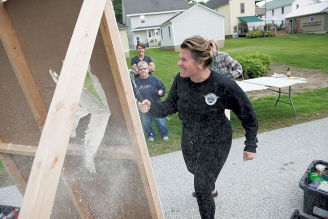 Christina Kumka swings a hammer to make a hole in drywall during Morgan Over's We Can Fix It class for women in Rutland - CALEB KENNA