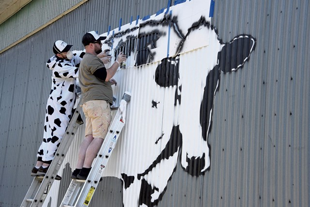 Middlesex artist DJ Barry (in cow suit) and New York City artist DJ Barry painting a World Cow in Montpelier - JEB WALLACE-BRODEUR