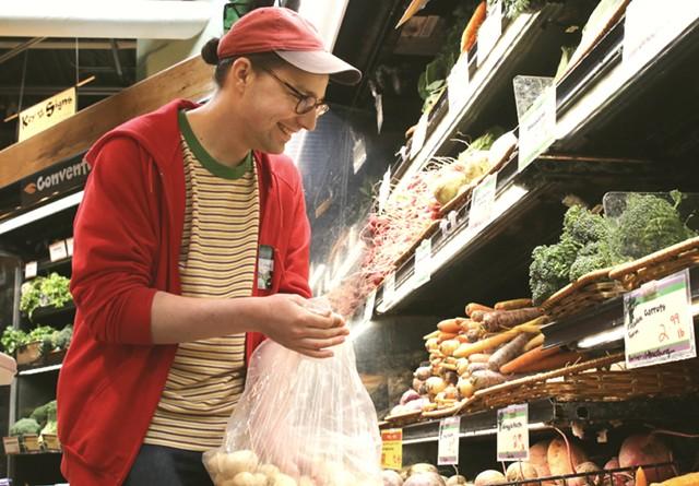 Connor Chilson stocks produce at City Market - COURTNEY LAMDIN