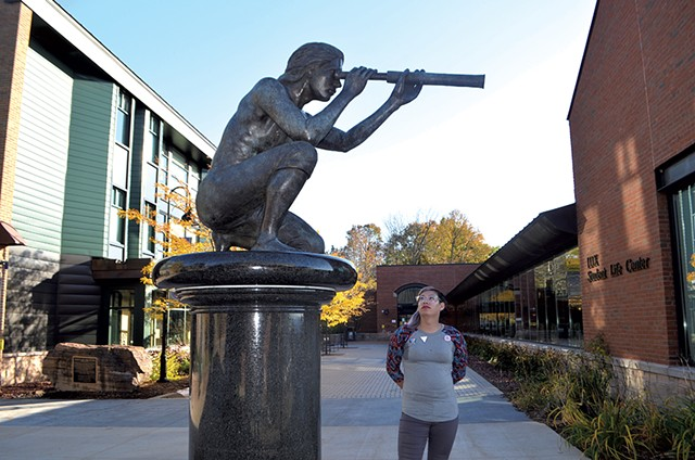 Jayy Covert standing next to the sculpture of Samuel de Champlain at Champlain College - MOLLY WALSH