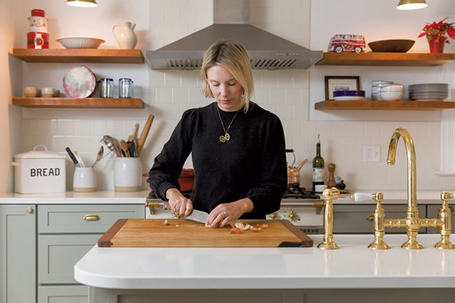 Becca Brown McKnight prepping dinner in the renovated kitchen of her Burlington home - OLIVER PARINI
