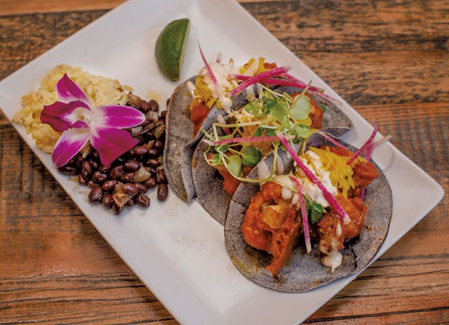 Buffalo cauliflower tacos with turmeric slaw and blue cheese crema, served with brown jasmine rice and Cuban black beans - GLENN RUSSELL