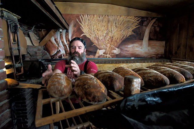 Trent Cooper placing a freshly baked sourdough bâtard on a cooling rack in Westford - GLENN RUSSELL