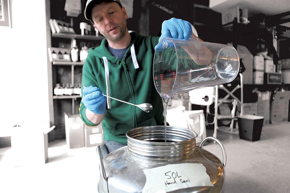 Alex Hilton adding glycerine to a batch of hand sanitizerRay Merola - KEVIN MCCALLUM