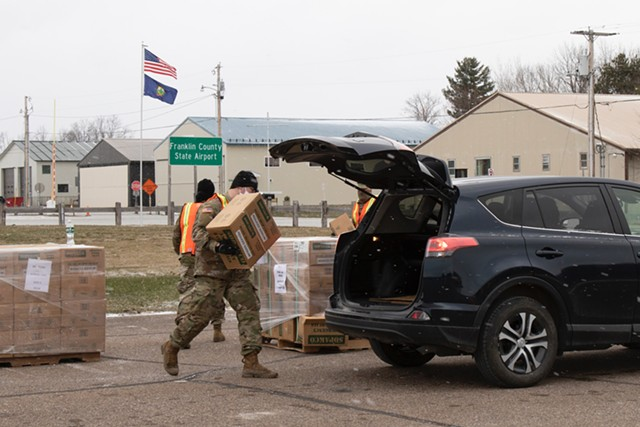 A member of the Vermont National Guard loading a case of MREs into a car in Swanton on April 22 - COURTESY OF VERMONT NATIONAL GUARD