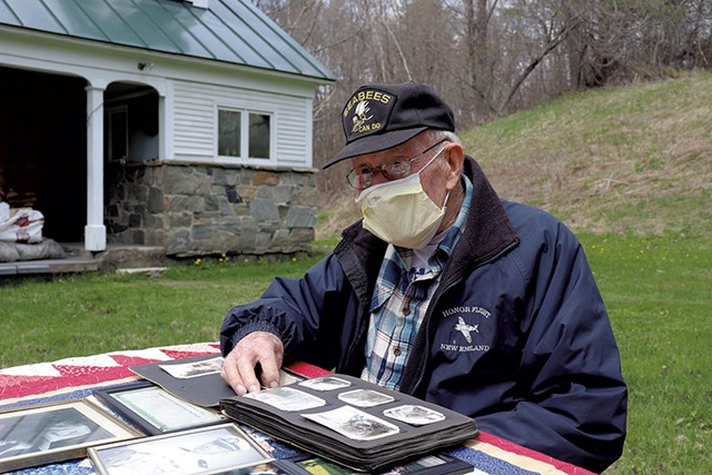 James J. Hasson, 94, flipping through World War II photos at his Cavendish home - DEREK BROUWER