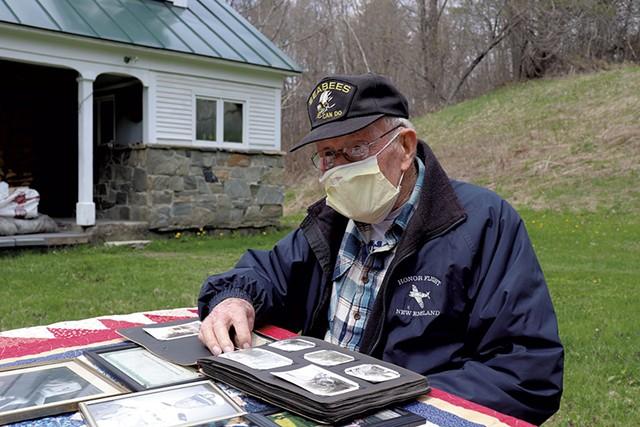 James J. Hasson, 94, flipping through World War II photos at his Cavendish home - DEREK BROUWER
