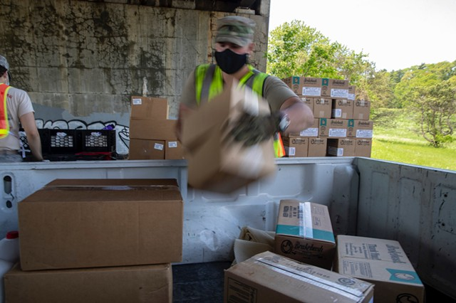 A guardsman loading food into a pickup truck Tuesday in Burlington - JAMES BUCK