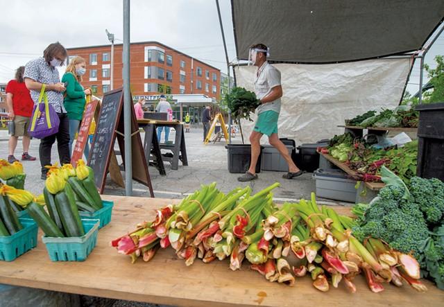 Robert Linck, from Fusda Farm, bringing mustard greens to a customer at the Capital City Farmers Market - JEB WALLACE-BRODEUR