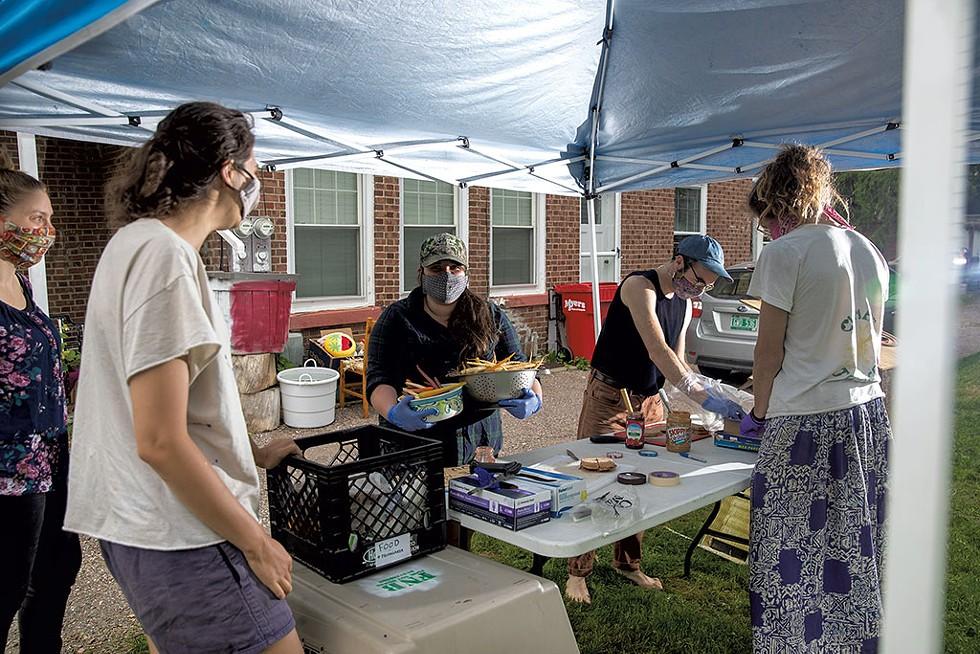 Food Not Bombs volunteers distributing food at the Marketplace Garage in Burlington - JEB WALLACE-BRODEUR