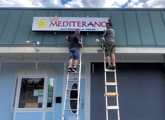 Cafe Mediterano owner Barney Crnalic (left) and friend, Mehmed Tuco, hang the sign at the new location. - COURTESY OF CAFE MEDITERANO