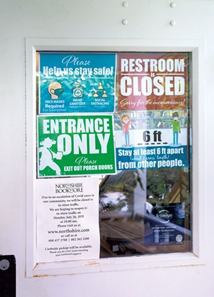 Northshire Bookstore door showing COVID-19 precautions and temporary closure due to suspected cases - CHRISTINE GLADE