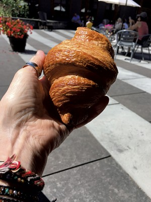 Dining on a croissant at King Arthur Baking's outdoor plaza - PAMELA POLSTON ©️ SEVEN DAYS