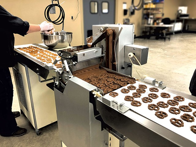 Enrobing machine coating pretzels with chocolate at Vermont Nut Free Chocolates - COURTESY OF VERMONT NUT FREE CHOCOLATES