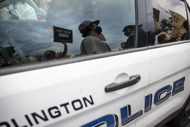 Demonstrators passing a police car in Burlington - FILE: JAMES BUCK ©️ SEVEN DAYS