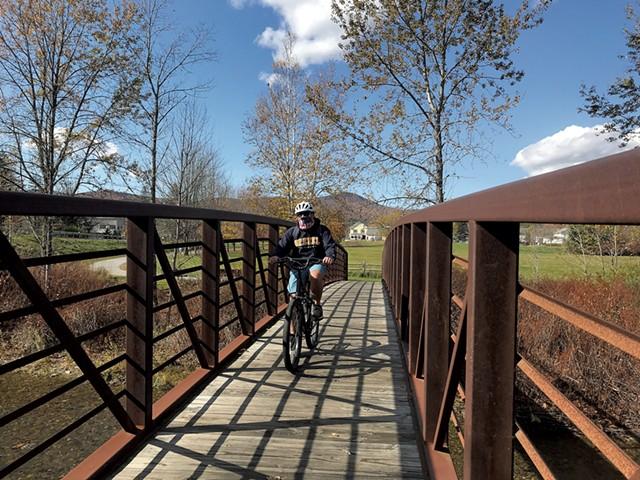 A cyclist on the Stowe Recreation Path - SALLY POLLAK ©️ SEVEN DAYS
