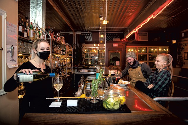 Bartender Gabriana Whiting (left) serving drinks, while Matt Cote-Wurzler of Shelburne and Maddie Marchionna of Burlington sit at the bar at the Daily Planet - DARIA BISHOP