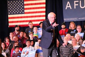 Sanders looks on as medics help an ailing audience member. - PAUL HEINTZ