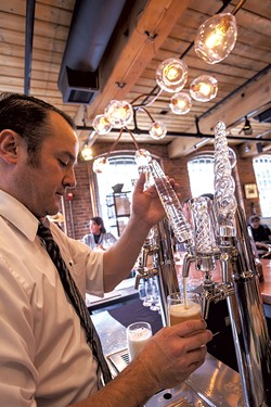 A bartender pulling draft beer with house-blown tap handles - TOM MCNEILL