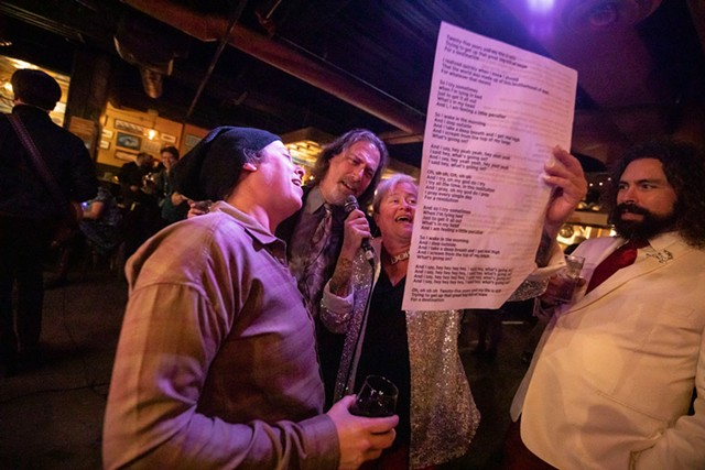 """Account executive Kaitlin Montgomery, writer Ken Picard, and art director Diane Sullivan sing """"The Weight"""" at Seven Days' 2019 holiday party. - FILE: LUKE AWTRY"""