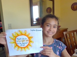 Sophia Oszurek with a colorful sign made to cheer up neighbors and passersby - MARY JANE OSZUREK