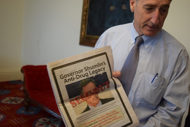 Thursday morning at the Statehouse, Gov. Peter Shumlin shows off an advertisement attacking him. - TERRI HALLENBECK