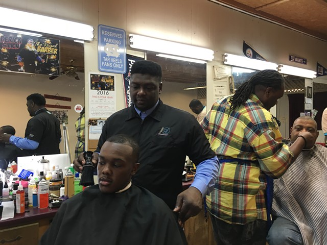 Barber Derick Simon at the Right Touch Barber Shop in Orangeburg, S.C. - PAUL HEINTZ