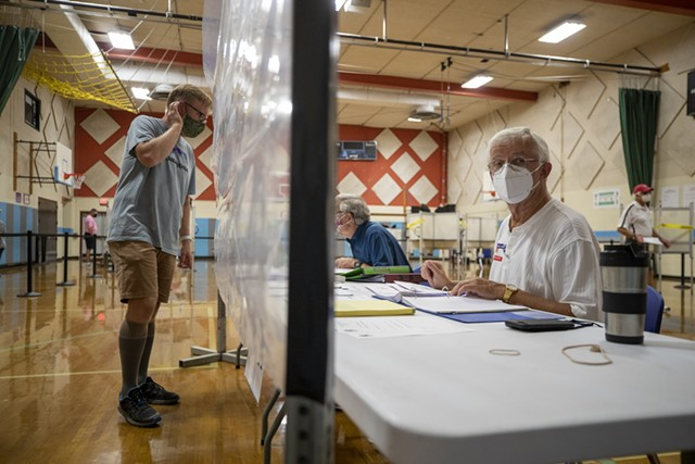 A poll worker behind a sheet of plastic in August - FILE: JAMES BUCK ©️ SEVEN DAYS