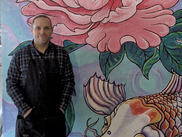 Brian Lewis in front of a mural by Tara Goreau at Filling Station - COURTESY OF BRIAN LEWIS