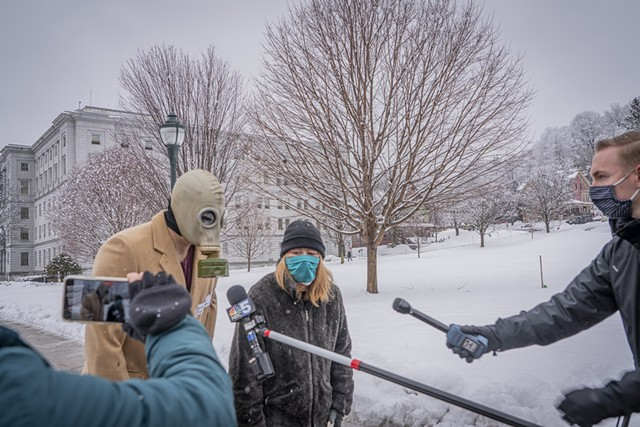 Thomas Gram, wearing mask, and Belynda Jestice talking to reporters on a sidewalk in front of the Statehouse - TERRY J. ALLEN