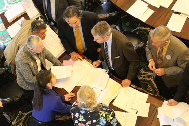 Senators and staff discuss public election finance legislation Wednesday in the Senate chamber. - PAUL HEINTZ