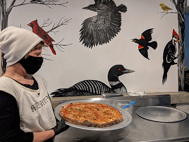 Hailey Cohn of Woodbelly Pizza in front of a mural by Frances Cannon - COURTESY OF KES MARCEL