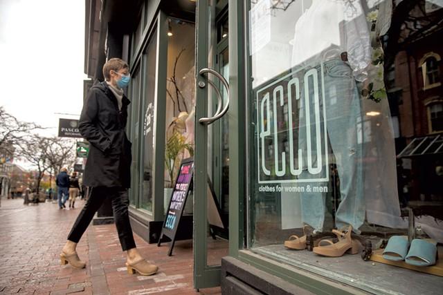 A customer walking into Ecco Clothes in Burlington - JAMES BUCK