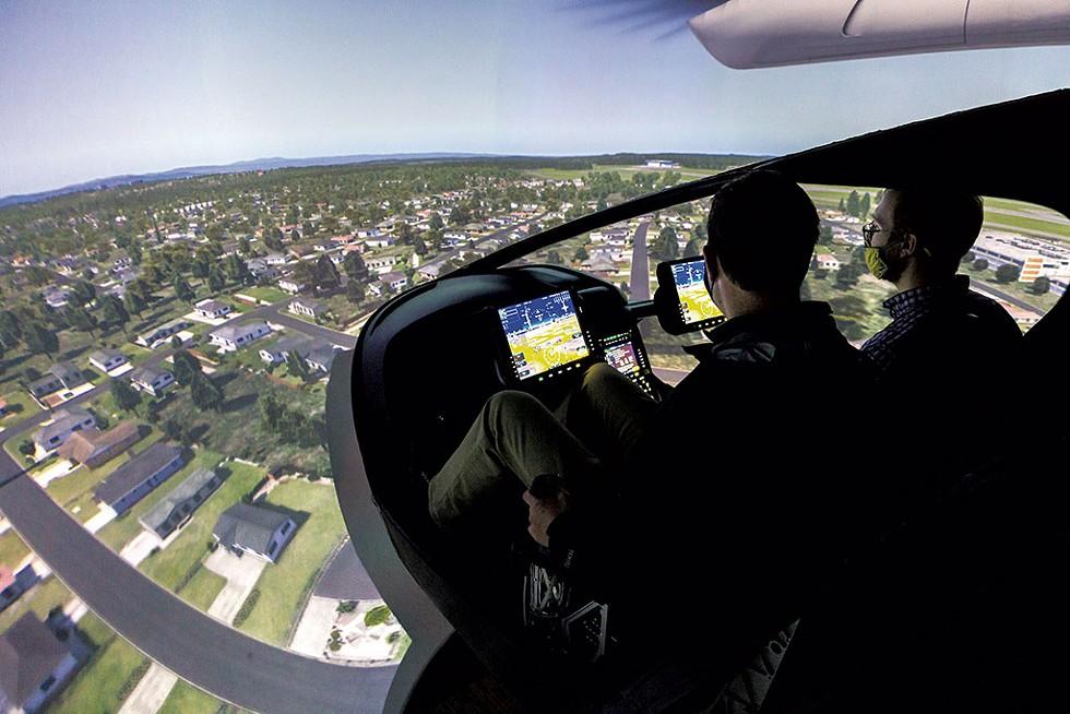 Kyle Clark (left) operating the flight simulator as reporter Derek Brouwer watches - OLIVER PARINI